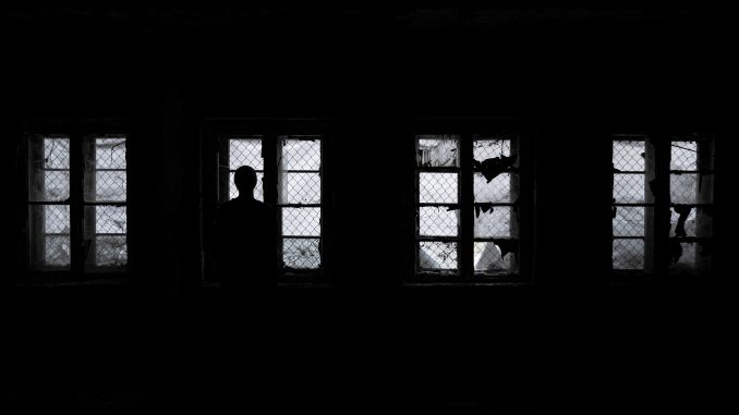 man silhouetted against bright window